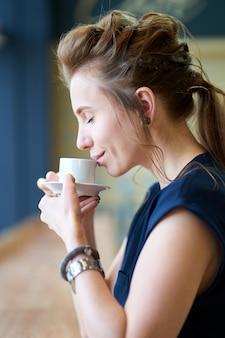 Rudzielec biała dziewczyna wącha aromat kawa podczas gdy siedzący w kawiarni