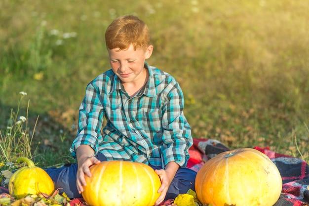 Rudzielec chłopiec trzyma żółtej bani