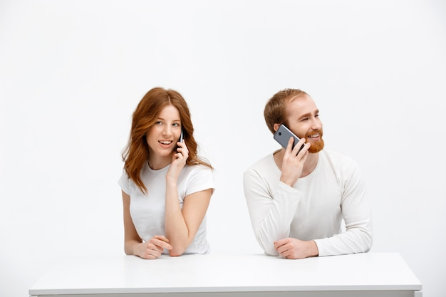 Rudzielec dziewczyna i mężczyzna opowiada smartphone