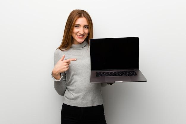 Rudzielec dziewczyna nad biel ścianą pokazuje laptop