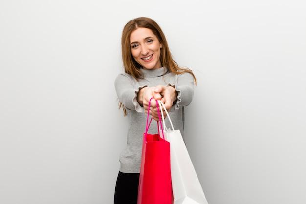 Rudzielec dziewczyna nad biel ścianą trzyma mnóstwo torba na zakupy