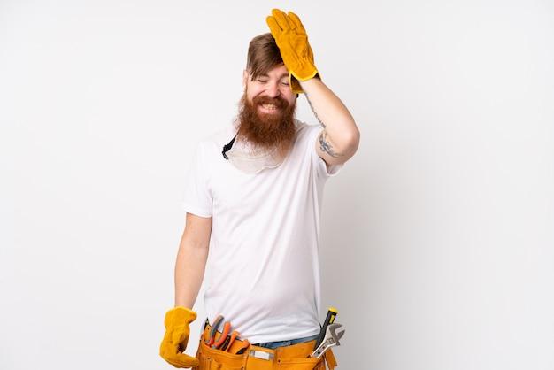 Rudzielec elektryka mężczyzna z długą brodą nad odosobnioną biel ścianą ma wątpliwości z zmieszanym wyrazem twarzy