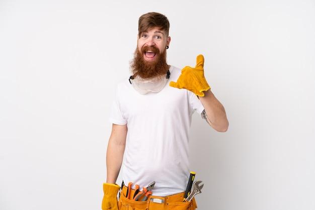 Rudzielec elektryka mężczyzna z długą brodą nad odosobnioną biel ścianą robi telefonu gestowi