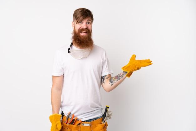 Rudzielec elektryka mężczyzna z długą brodą nad odosobnioną biel ścianą trzyma copyspace imaginacyjnego na palmie