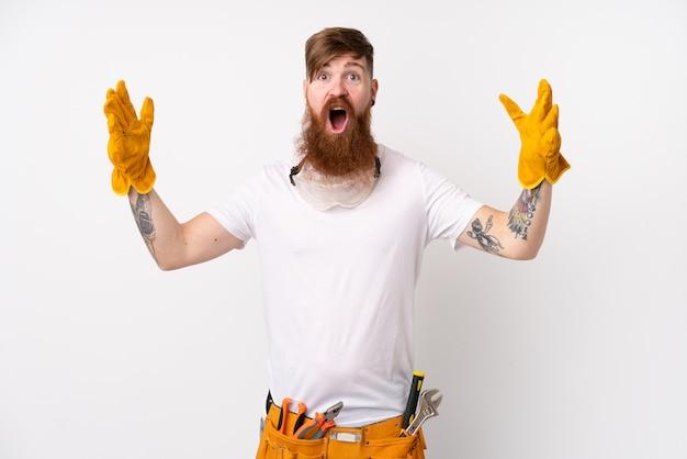 Rudzielec elektryka mężczyzna z długą brodą nad odosobnioną biel ścianą z niespodzianka wyrazem twarzy