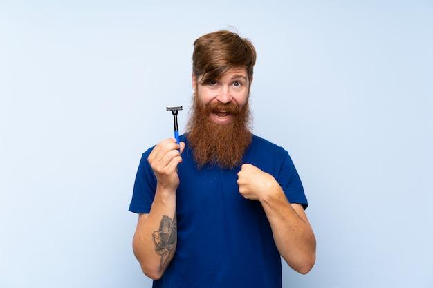 Rudzielec goli brodę nad odosobnioną błękit ścianą z niespodzianka wyrazem twarzy