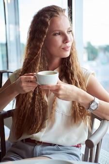 Rudzielec kędzierzawa biała chuda dziewczyna w białej koszula pije kawę w kawiarni i patrzeje okno