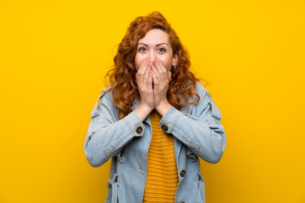 Rudzielec kobieta nad odosobnionym kolorem żółtym z niespodzianka wyrazem twarzy