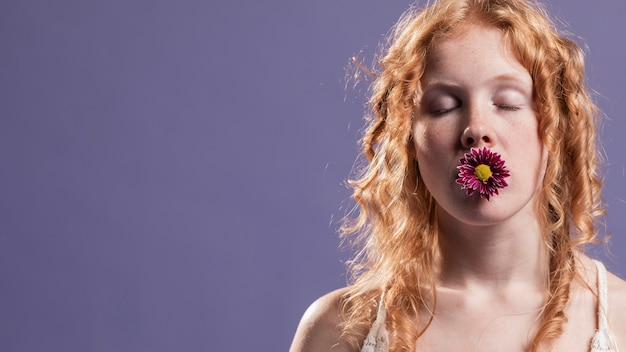 Rudzielec kobieta pozuje z kwiatem nad jej usta i kopii przestrzenią