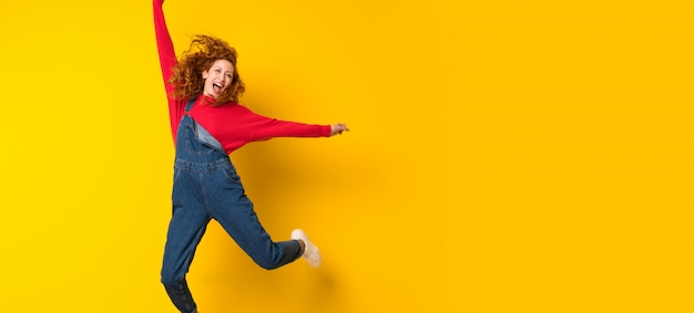 Rudzielec kobieta skacze nad odosobnioną kolor żółty ścianą z kombinezonami