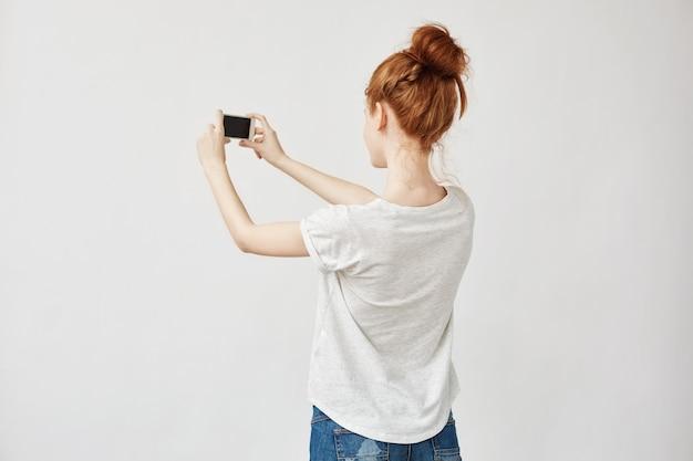 Rudzielec kobieta trzyma telefon stoi z powrotem.