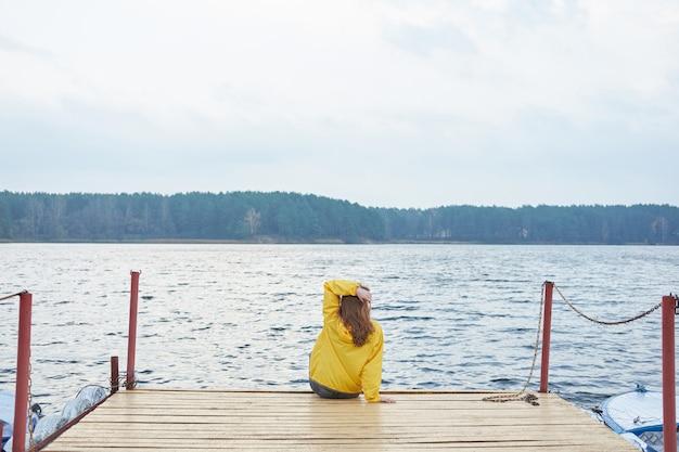 Rudzielec kobieta w żółtym płaszczu siedzi na molo jeziora i patrzeje daleko.