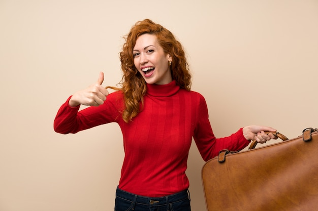 Rudzielec kobieta z golfowym pulowerem trzyma rocznik teczkę