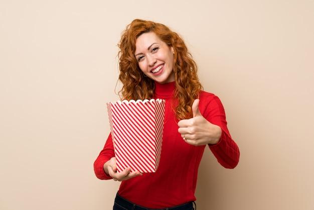 Rudzielec kobieta z golfowym swetrem trzyma miskę popcorns