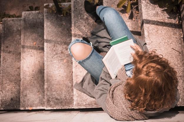 Rudzielec kobieta z rozpieczętowaną książką na kamiennym schodku