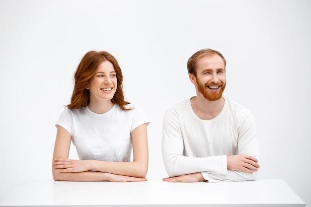Rudzielec mężczyzna i kobieta śmia się nad stołem