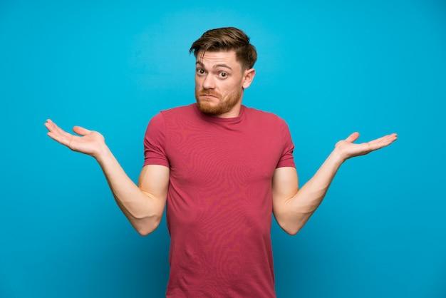 Rudzielec mężczyzna na odosobnionej błękit ścianie ma wątpliwości z zmieszanym wyrażeniem twarzy