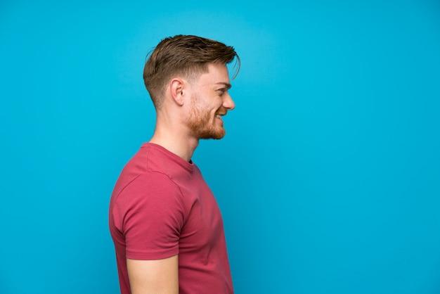 Rudzielec mężczyzna na odosobnionej błękit ściany pozyci i patrzeć strona