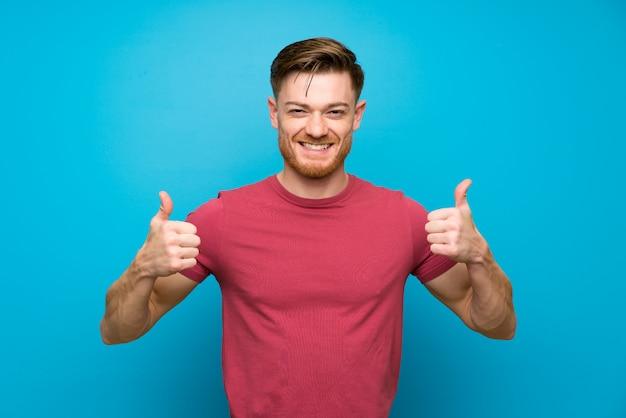 Rudzielec mężczyzna na odosobnionej błękitnej ścianie daje aprobata gestowi