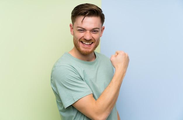 Rudzielec mężczyzna nad kolorową ścianą świętuje zwycięstwo