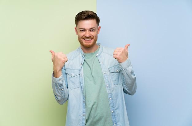 Rudzielec mężczyzna nad kolorowym z aprobatami gestykuluje i ono uśmiecha się