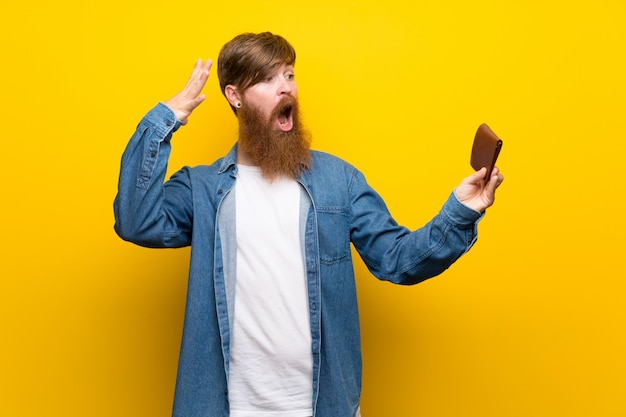 Rudzielec mężczyzna trzyma długą portfel z długą brodą nad odosobnioną kolor żółty ścianą