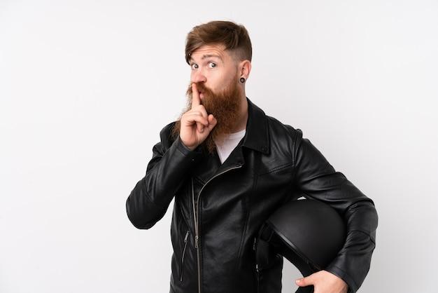 Rudzielec mężczyzna trzyma hełm motocykl nad odosobnioną biel ścianą z długą brodą robi cisza gestowi