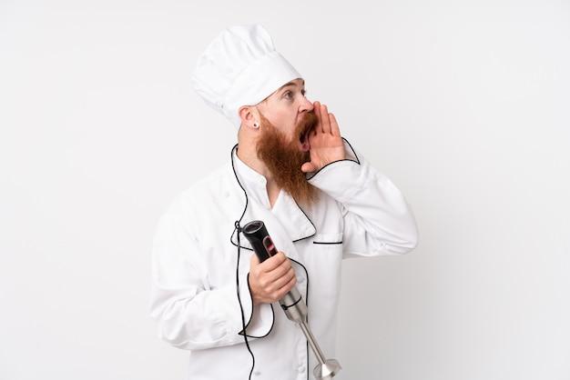 Rudzielec mężczyzna używa ręki blender nad odosobnioną biel ścianą krzyczy z usta szeroko otwarty