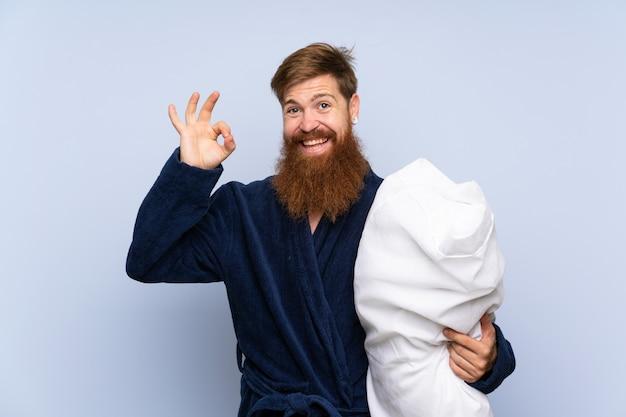 Rudzielec mężczyzna w piżamie pokazuje ok znaka z palcami