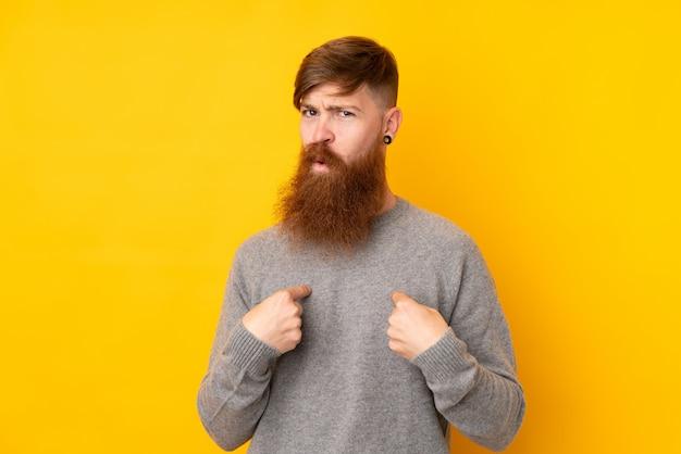 Rudzielec mężczyzna wskazuje na siebie z długą brodą nad odosobnioną kolor żółty ścianą