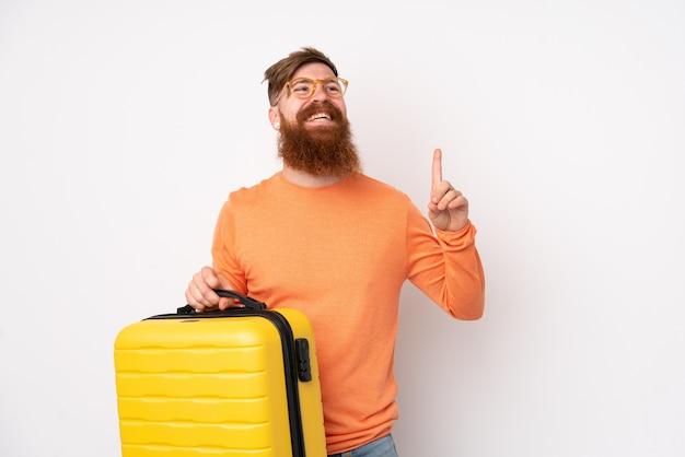 Rudzielec mężczyzna z długą brodą nad biel ścianą w wakacje z podróży walizką i wskazywać up