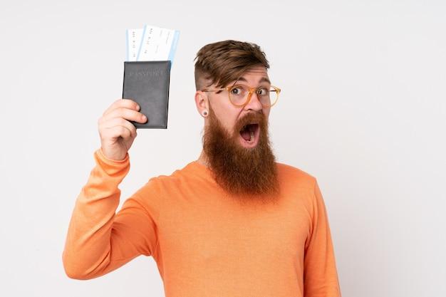 Rudzielec mężczyzna z długą brodą nad odosobnioną biel ścianą szczęśliwą w wakacje z paszportem i samolotowymi biletami