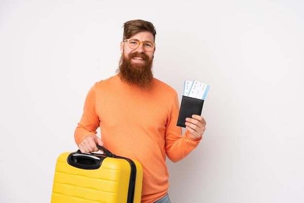 Rudzielec mężczyzna z długą brodą nad odosobnioną biel ścianą w wakacje z walizką i paszportem