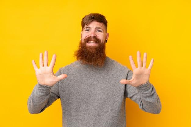 Rudzielec mężczyzna z długą brodą nad odosobnioną kolor żółty ścianą liczy dziesięć z palcami