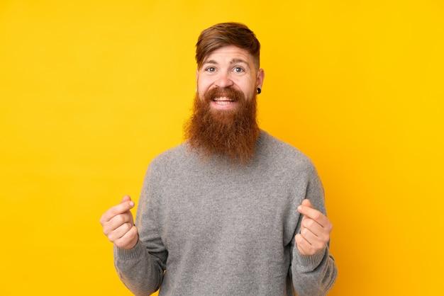 Rudzielec mężczyzna z długą brodą nad odosobnioną kolor żółty ścianą robi pieniądze gestowi