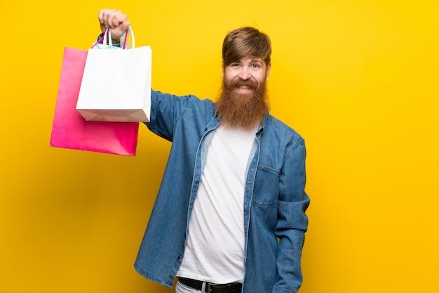Rudzielec mężczyzna z długą brodą nad odosobnioną kolor żółty ścianą trzyma mnóstwo torba na zakupy