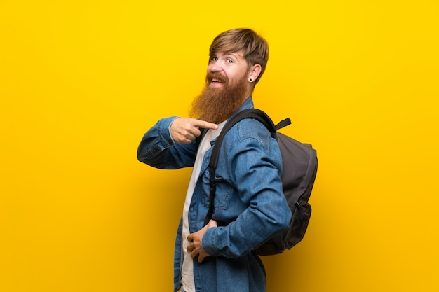 Rudzielec mężczyzna z długą brodą nad odosobnioną kolor żółty ścianą z plecakiem