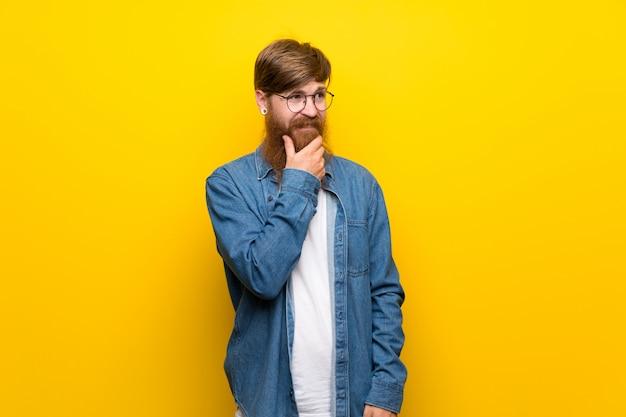 Rudzielec mężczyzna z długą brodą nad odosobnioną kolor żółty ścianą z szkłami
