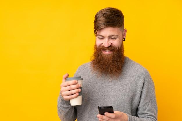 Rudzielec mężczyzna z długą brodą nad odosobnioną kolor żółty ściany mienia kawą zabrać i wiszącą ozdobą