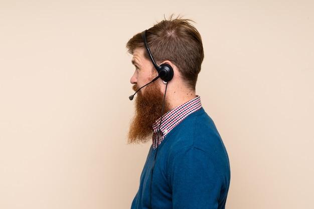 Rudzielec mężczyzna z długą brodą pracuje z słuchawki