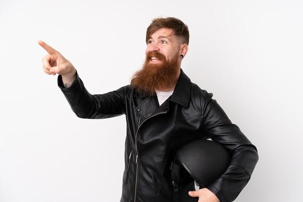 Rudzielec mężczyzna z długą brodą trzyma hełm motocyklowy nad odosobnionym biel ściany macaniem na przejrzystym ekranie