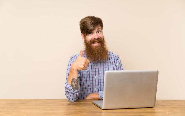 Rudzielec mężczyzna z długą brodą w stole z laptopem daje aprobata gestowi