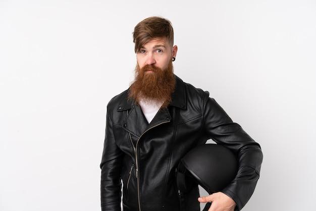 Rudzielec mężczyzna z długim brodą trzyma motocyklu hełm nad odosobnioną biel ścianą smutną