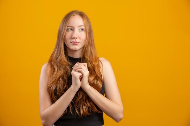 Rudzielec młoda dziewczyna myśleć pomysł nad odosobnioną kolor żółty ścianą.