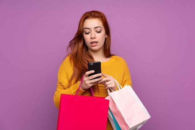 Rudzielec młoda kobieta trzyma torba na zakupy i pisze wiadomości z jej telefonem komórkowym przyjaciel