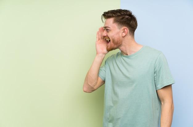 Rudzielec nad kolorową ścianą krzyczy z szeroko otwarty usta