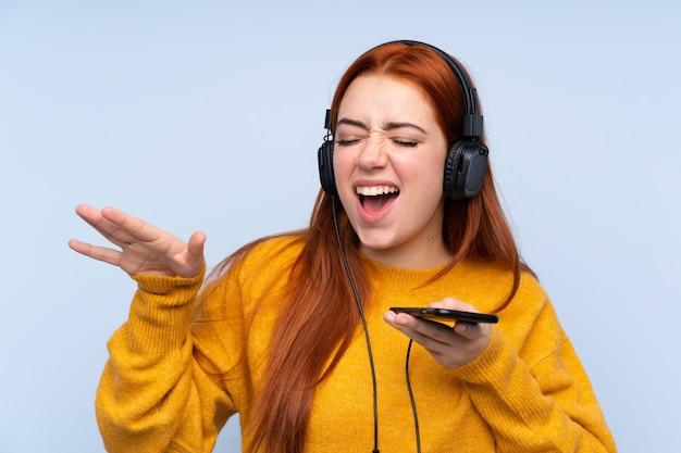 Rudzielec nastolatka dziewczyna nad odosobnioną błękit ściany ścianą słucha muzykę z telefonem komórkowym i śpiewa
