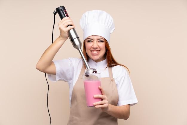 Rudzielec nastolatka kobieta używa ręka blender nad odosobnioną ścianą