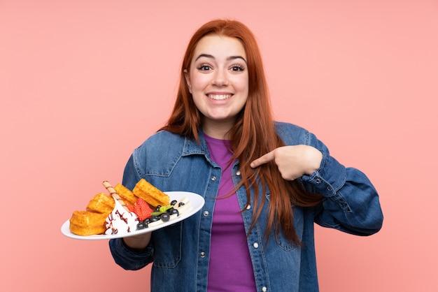 Rudzielec nastolatka kobiety mienia gofry nad odosobnioną menchii ścianą z niespodzianka wyrazem twarzy