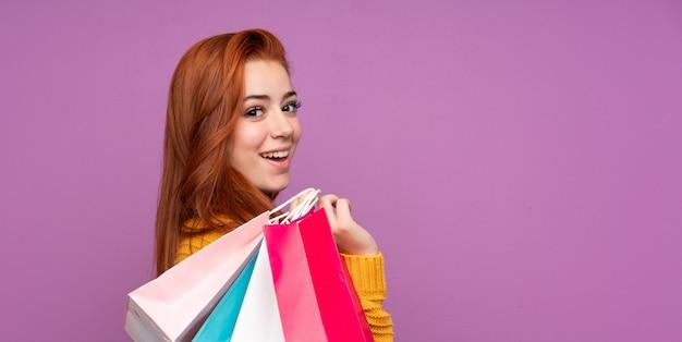 Rudzielec nastolatka kobiety mienia torba na zakupy i ono uśmiecha się